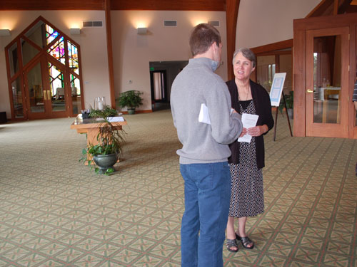Debbie sharing information in the narthex at St. Alphonsus.